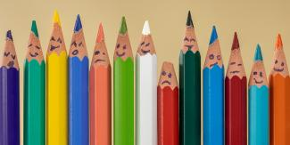 Image of pencils with faces lined up to portray diversity